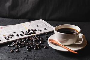 Tasse Kaffee und Kaffeebohnen auf Zeitung foto