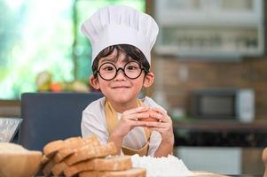 süßer kleiner asiatischer glücklicher Junge, der am Kochen interessiert ist