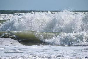 Meereswellen, die am Strand krachen foto