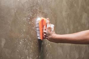 Nahaufnahme einer Person, die eine Wand schrubbt