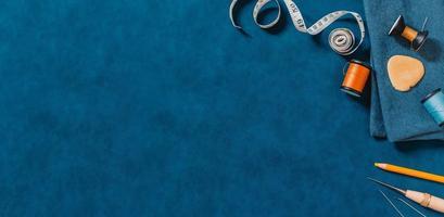 blauer strukturierter Hintergrund mit Nähwerkzeugen