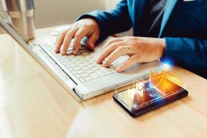 Geschäftsmann mit Laptop- und Smartphone-Bildschirmanzeige foto
