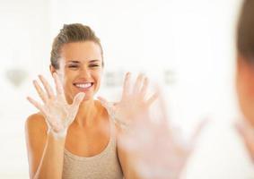 glückliche junge Frau, die seifige Hände zeigt foto