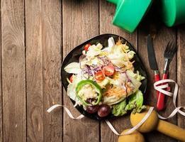 Kurzhanteln, Maßband und gesunder Lebensmittelsalat auf hölzernem Hintergrund foto