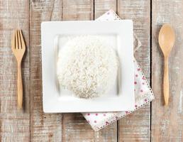 Schüssel voll Reis und Löffel auf weißem Hintergrund