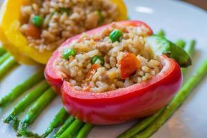 Reispilaf mit buntem Gemüse in rotem Paprika