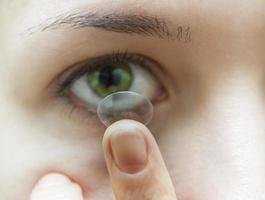 Frau, die Kontaktlinse ins Auge setzt foto