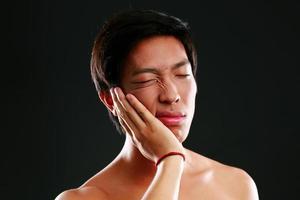 junger asiatischer Mann mit Zahnschmerzen foto