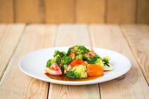 Tomaten und Brokkoli unter Rühren braten. in Platte auf Tisch foto