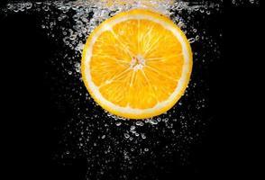 Nahaufnahme Orangenscheibe in Wasser mit Blasen