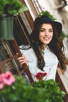 junge Frau mit Hut im städtischen Hintergrund, der Freizeitkleidung trägt