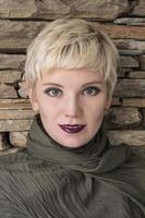 Frauenporträt blond. Modefrisur, Haarschnitt, Make-up in Grautönen. foto
