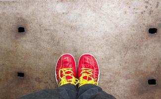 Fußkonzept mit roten Schuhen auf Stahl