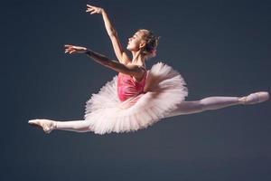 schöne Balletttänzerin auf grauem Hintergrund. Ballerina ist