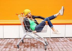 Modefrau reiten, die Spaß im Einkaufswagenwagen hat
