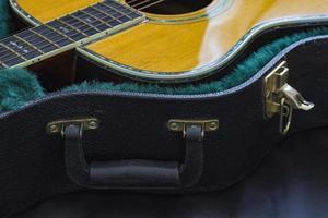 Teil der Akustikgitarre mit offenem Gitarrenkoffer.