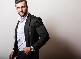 eleganter junger hübscher Mann im schwarzen klassischen Kostüm. foto