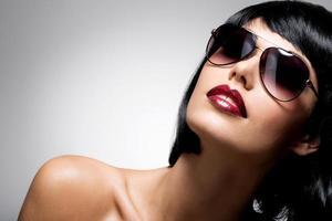 schöne brünette frau mit geschossen frisur mit roter sonnenbrille foto