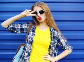 Mode hübsches Mädchen, das eine bunte Kleidung trägt, die Spaß hat foto