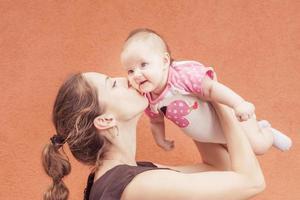 glückliche Mutter, die ihr Baby am Wandhintergrund küsst foto