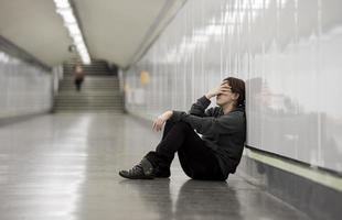 junge traurige Frau im Schmerz allein am U-Bahn-Tunnel niedergedrückt foto