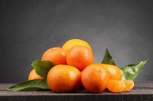 Mandarinen mit Blättern auf Holztisch auf grauem Hintergrund foto