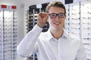 Mann wählt neue Brille bei Optikern foto