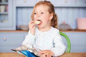 junges Mädchen, das am Tisch sitzt und Kartoffelchips isst foto