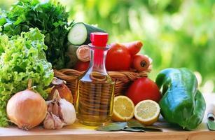 Olivenöl und Gemüse auf dem Tisch foto