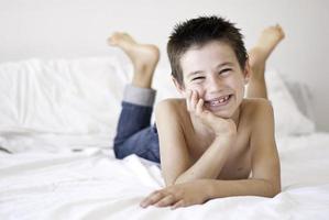 glücklicher Junge, der auf einem weißen Bett aufwirft foto