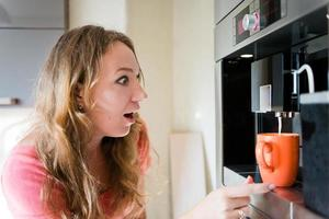 glückliche junge Frau, die Kaffeetassenmaschine Kücheninnenraum macht foto