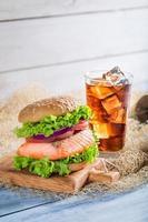 hausgemachter Burger mit Fisch serviert mit kaltem Getränk foto