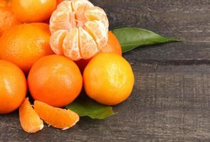 Mandarinen mit Blättern auf grauem Holztisch foto
