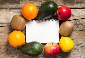 leerer Rezeptnotizblock mit verschiedenen Früchten herum auf Holzhintergrund foto