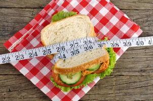 Sandwich mit Maßband auf Holzhintergrund foto