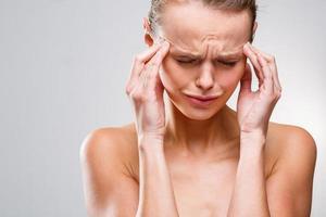 schöne Frau mit akuten Kopfschmerzen foto