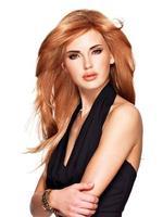 schöne Frau mit langen glatten roten Haaren im schwarzen Kleid