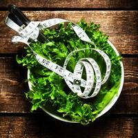 Salat mit Fitnessmaßband über Holzhintergrund foto