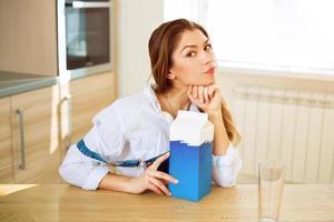 junge schöne Frau, die am Tisch sitzt foto