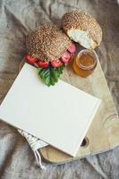 Kochbuch gerahmtes Frühstück von Beeren mit einem Brötchen und Honig foto