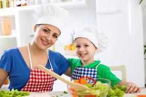 lächelnde glückliche Mutter und Kind mit Kochmütze