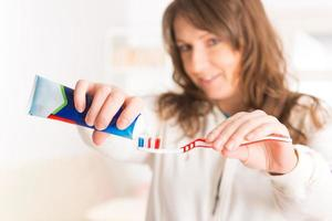 Frau hält Zahnbürste und Zahnpasta foto