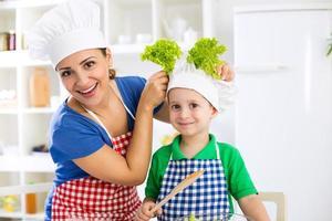lächelnde schöne Mutter und Kind mit Kochmütze bereiten Lettu vor