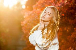 junge Frau auf einem Hintergrund des roten und gelben Herbstes