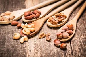 Nüsse auf Holztisch mischen, gesundes veganes Essen.
