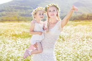 Familie Mutter und Kind im Feld der Gänseblümchenblumen foto