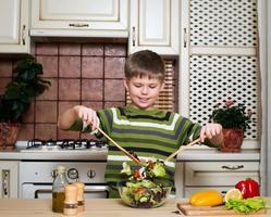 lächelnder Junge, der Gemüsesalat mischt. gesundes Essen. foto