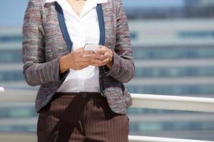 Nahaufnahmeporträt einer Geschäftsfrau, die Handy hält foto
