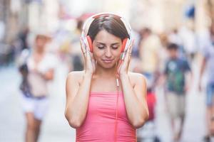 schöne junge Frau, die Musik in der Stadt hört foto