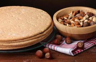 Kuchen und Nüsse auf Holztisch auf braunem Hintergrund foto